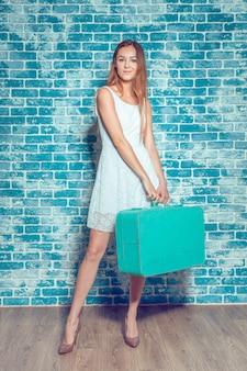 スーツケースを持つ若いきれいな女の子