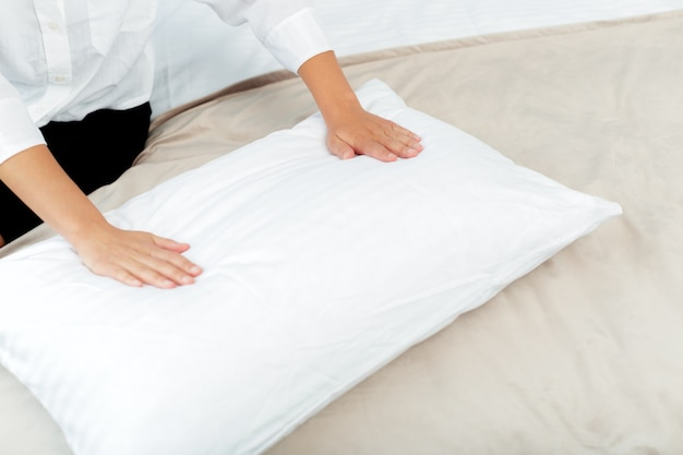 Молодая горничная делает кровать в гостиничном номере