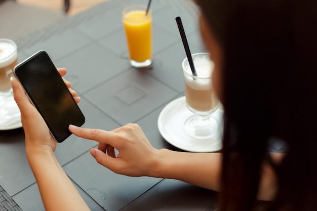 Портрет красивой девушки, используя ее мобильный телефон в кафе