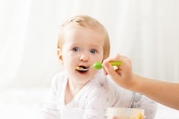 スプーンで餌をやる小さな赤ちゃん