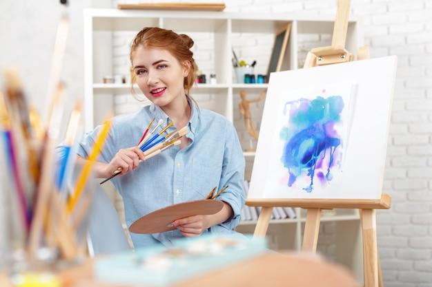 イーゼルに抽象絵画を描く若い美しい女性アーティスト