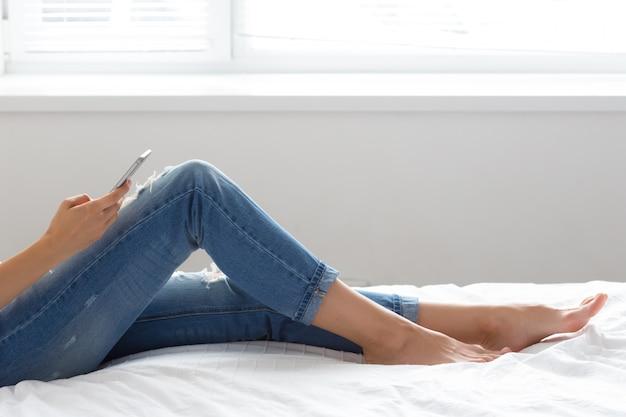 Женщина проверяет сотовый телефон на кровати