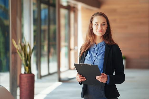 オフィスでクリップボードと幸せな美しいビジネス女性。