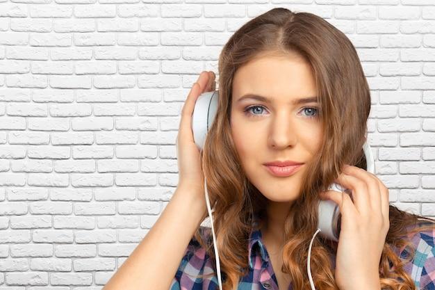 幸せな若い女が音楽を聴く