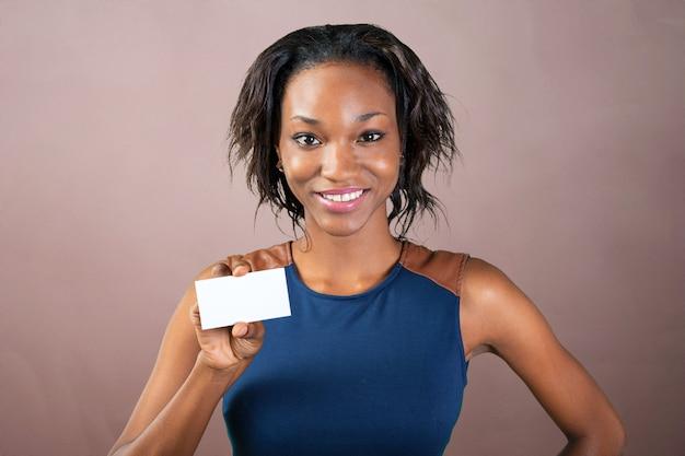 Красивая женщина с идеальной улыбкой держит визитку
