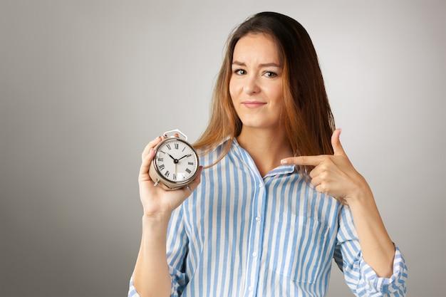 魅力的な女性は目覚まし時計を保持しています。営業時間管理のコンセプト