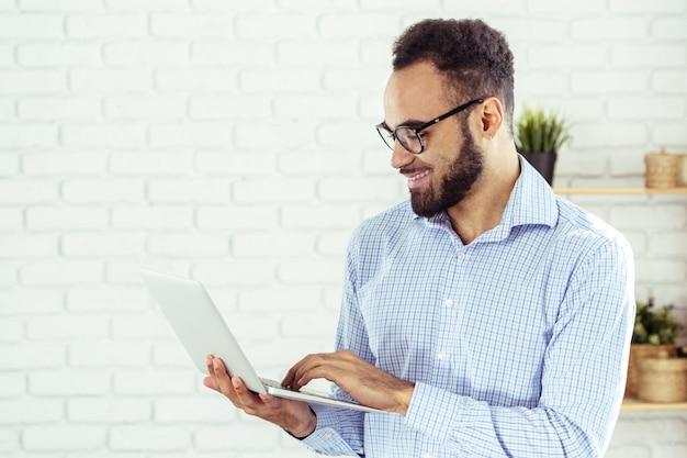 ラップトップコンピューターを使用して幸せなアフリカ系アメリカ人の男の肖像