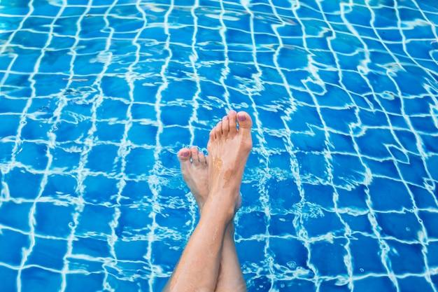 スイミングプールで美しい女性の足。
