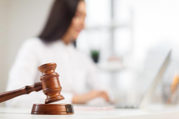 テーブルの上の木製の小槌。法廷で働く弁護士。