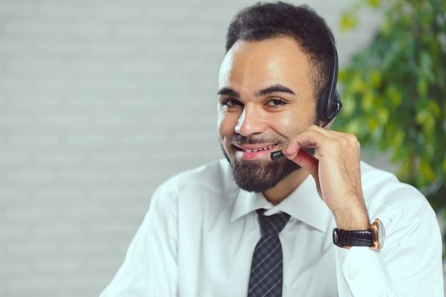 ヘッドフォンを持つ男。クライアントと話すコールセンターのオペレーター