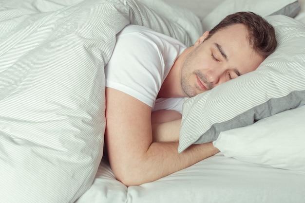 Молодой человек спит на кровати в спальне