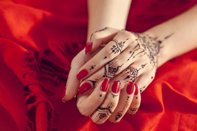 一時的な刺青と手入れの行き届いた赤い手