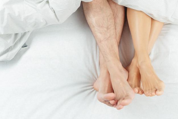 美しいカップルが一緒にベッドに横になっています。