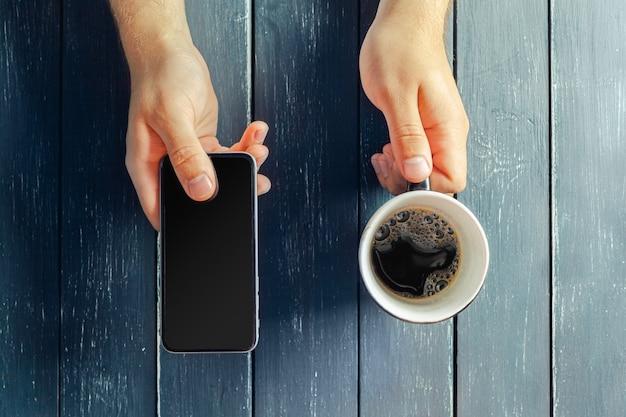木製のテーブルに温かい飲み物のマグカップを両手