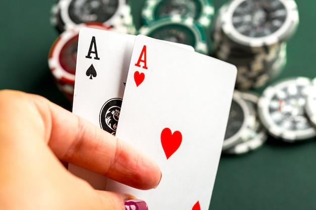 緑色のテーブルの上の火かき棒のためのカードとチップ