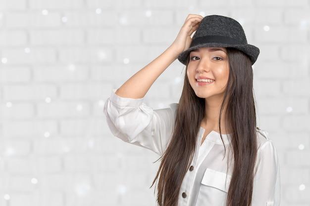 麦わら帽子のポーズを着て美しい若い女性