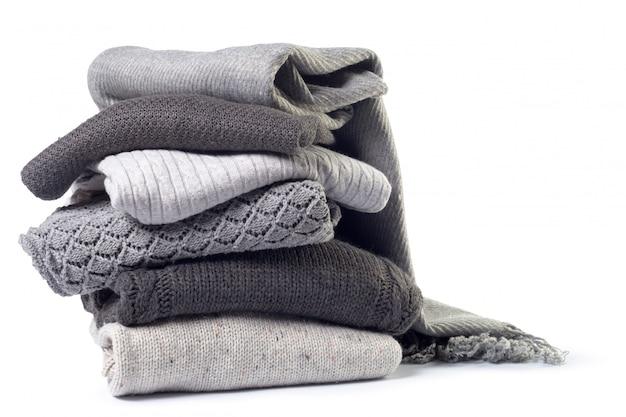 白で隔離される様々なセーターのスタック