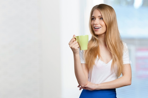 Молодая женщина пьет кофе или чай
