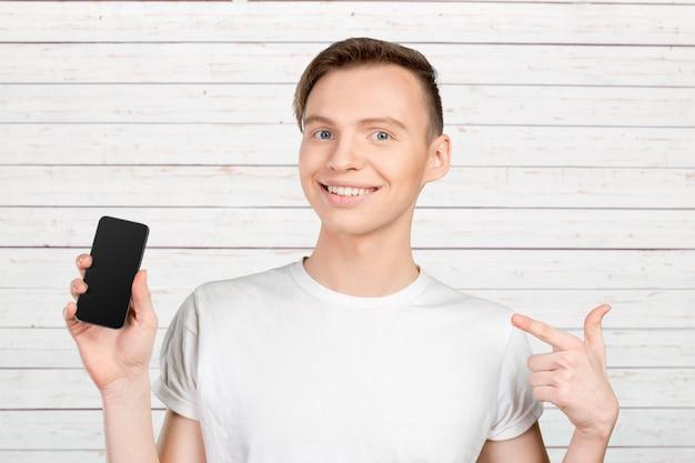 若い男が空白のスマートフォンの画面を表示
