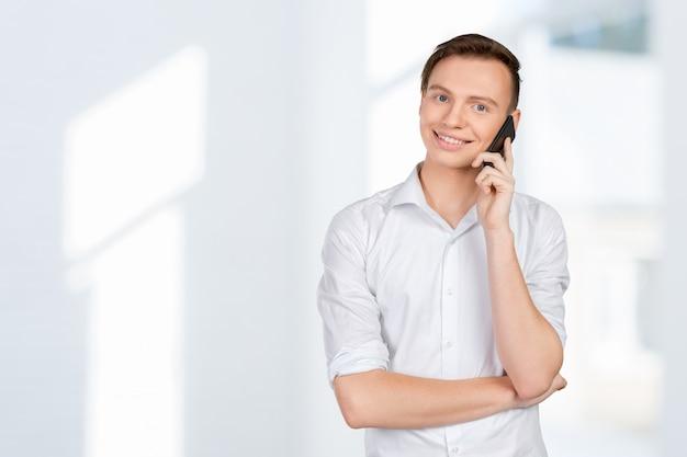 携帯電話で話している若い笑みを浮かべて男