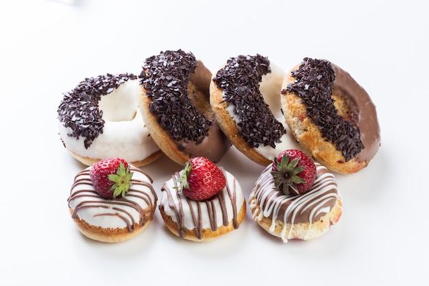 Различные пончики на белом фоне