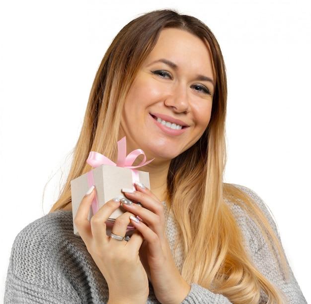 Молодая женщина и подарок, изолированные на белом