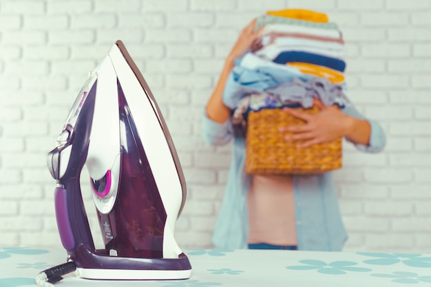 アイロン台の上に洗濯物の巨大な山をもたらす主婦