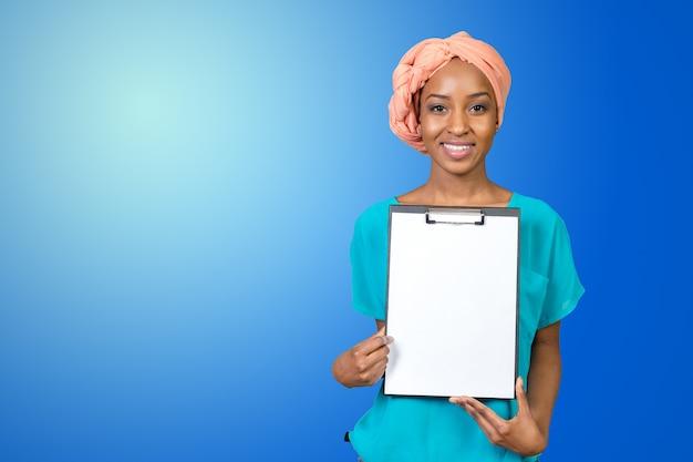 Молодая красивая афро-американская женщина показывая доску сзажимом для бумаги