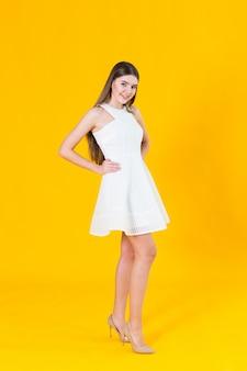 スタジオで黄色の背景にポーズをとって素敵な春のドレスで美しい若いブロンドの女性