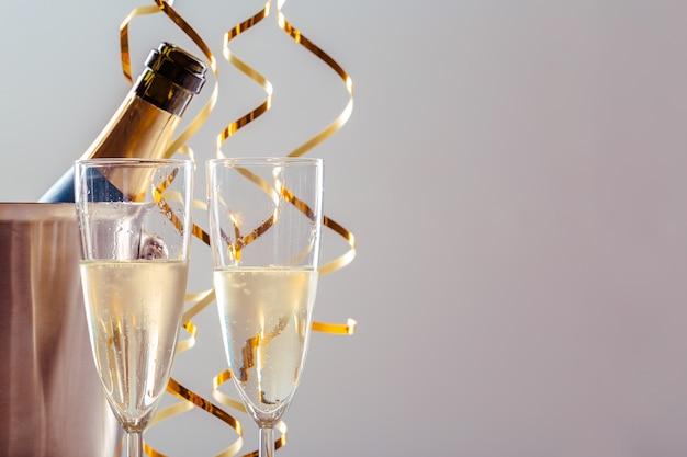 金属製の容器にボトルとシャンパンのペアガラス。新年のお祝い