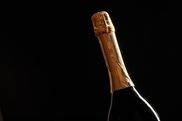 Бутылка шампанского на черном фоне.