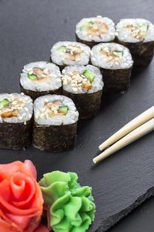 日本食レストラン、黒のスレート板に巻き寿司。