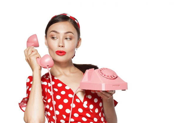 ピンナップスタイルに身を包んだ携帯電話を持つ美しい若い女性の肖像画。