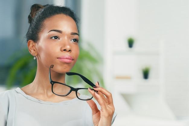 彼女の眼鏡を保持している若いアフリカ人女性