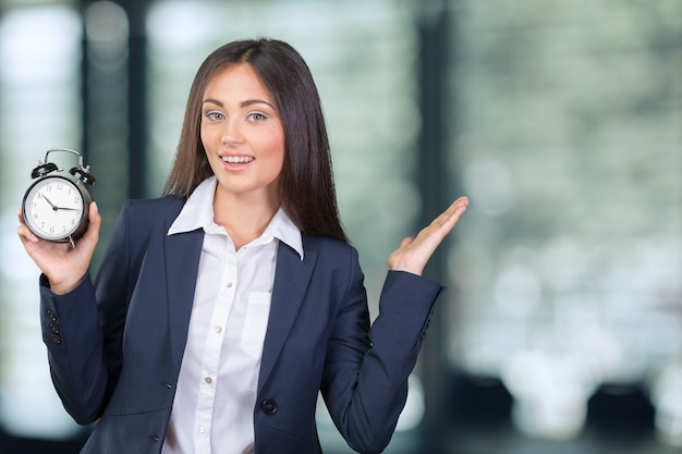 Молодая женщина, держащая часы. концепция тайм-менеджмента.