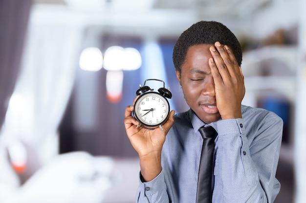 黒人男性の目覚まし時計を保持