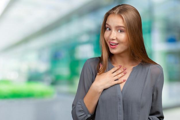 自分を指している若いビジネス女性