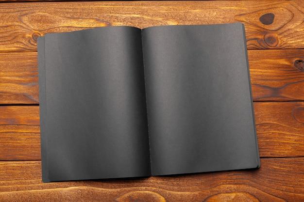 木製のテーブルの上の黒い紙のモックアップ