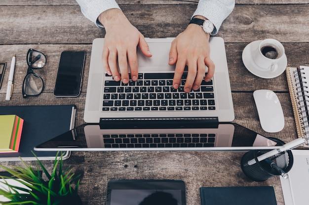 Бизнесмен на работе. крупным планом вид сверху человека, работающего на ноутбуке