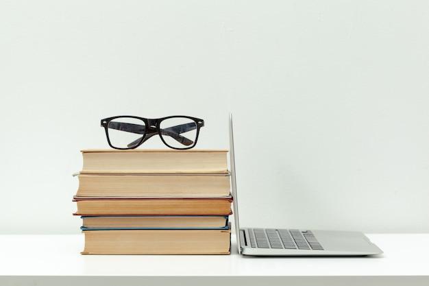作業机。オープンノートパソコン、書籍、その他の事務用品