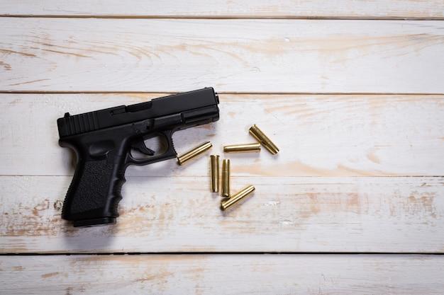 Ручной пистолет с патронами на деревянный стол