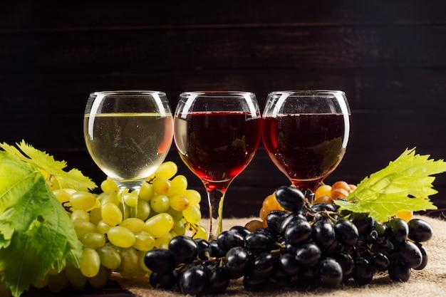 Бокал и гроздь винограда на деревянный стол