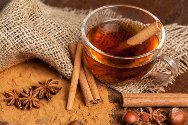 木製のテーブルの上の芳香のホットシナモンティーカップ