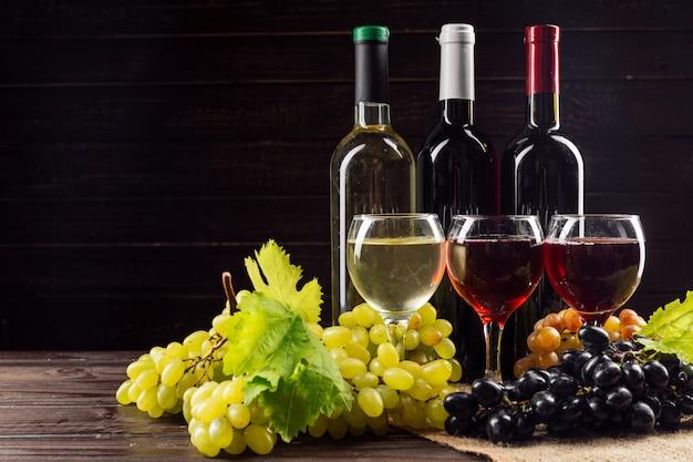 ワインの瓶とブドウの木のテーブル