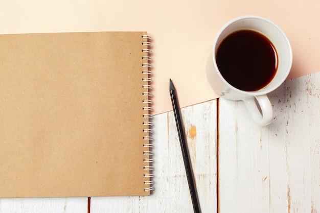空白のメモ帳、鉛筆でオフィスの木のテーブル。