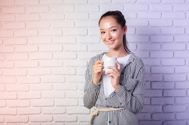 レンガ壁の背景にコーヒーのカップを保持している若い女性