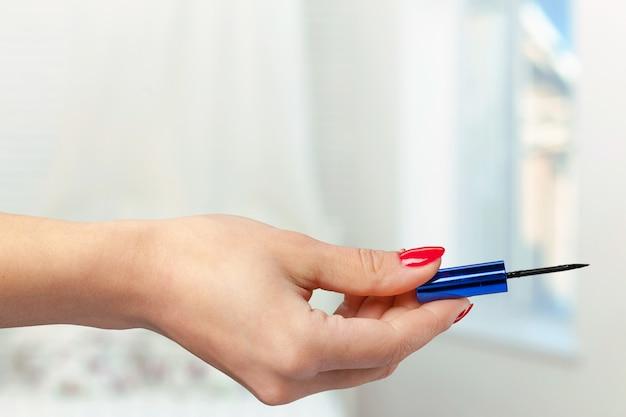 プロのメイクアップブラシを持つ女性の手