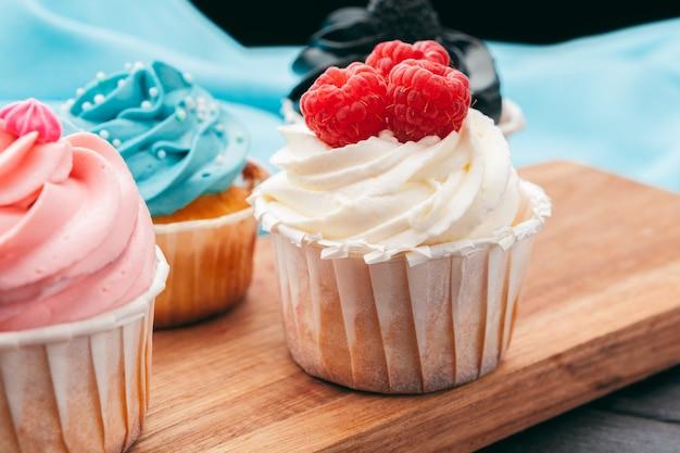 さまざまなフロスティングフレーバーで艶をかけられたいくつかの退廃的なグルメカップケーキのクローズアップ