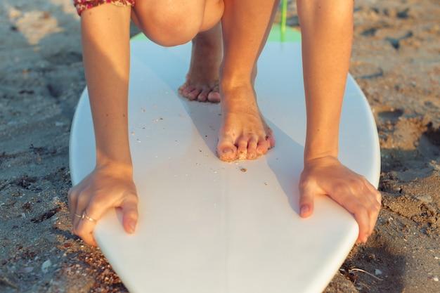 Женские ножки и доска для серфинга