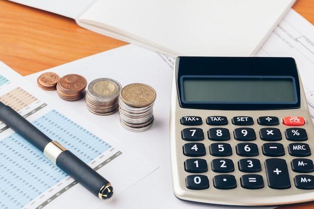 木のテーブル、アカウントの概念、財務および事業の成長に関するグラフ紙とお金のコインの山